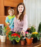 Mother and  toddler are transplanting and watered potted flowers Royalty Free Stock Images