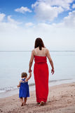 Mother with  toddler walking  on sand beach Stock Images