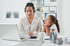 When mother is too busy. Lonely preteen girl looking at her busy mother in office Stock Image