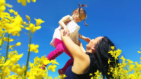 Mother toss up her daughter in yellow field royalty free stock photos