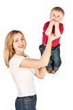 Mother tossing up amazed child. Mother tossing up surprised child on white background Royalty Free Stock Images