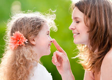 Mother touching her daughter on her nose Royalty Free Stock Images