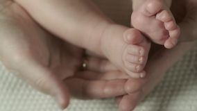 Mother is touching and stroking the baby feet. Close up stock video footage