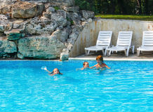 Mother train children to swim in the pool. Royalty Free Stock Photo