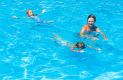 Mother train children to swim in the pool. Stock Photography
