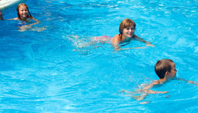 Mother train children to swim in the pool. Royalty Free Stock Image