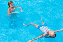 Mother train her daughter to swim in the pool. Stock Images