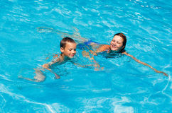 Mother train her son to swim in the pool. Royalty Free Stock Images