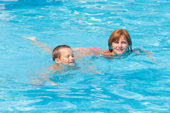 Mother train her son to swim in the pool. Stock Images