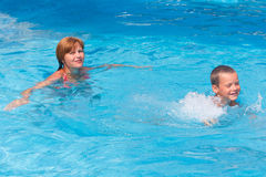Mother train her son to swim in the pool. Royalty Free Stock Photography