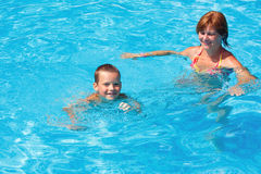 Mother train her son to swim in the pool. Stock Photos