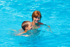 Mother train her son to swim in the pool. Stock Photo