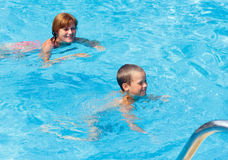 Mother train her son to swim in the pool. Royalty Free Stock Image