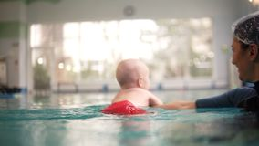 Mother or trainer teach the baby boy to swim in the indoors swimming pool, holds him under the water. Happy child enjoy. The swimming in the water. Close up of stock footage