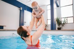 Mother traning her newborn baby to float in swimming pool. White Caucasian mother traning her newborn baby to float in swimming pool. Happy mom parent holding Stock Image