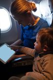 Mother traveling on a plane with her small son Stock Photos