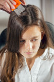 Mother treating daughter's hair against lice Royalty Free Stock Images
