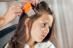 Mother treating daughter's hair against lice. Selective focus Royalty Free Stock Photo
