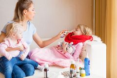 Mother treating her child`s sore throat. While sitting at home Stock Photos