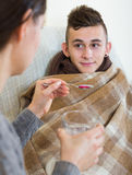 Mother treating teenage boy with syrup at home Stock Photography