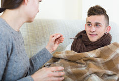 Mother treating teenage boy with syrup at home Royalty Free Stock Images