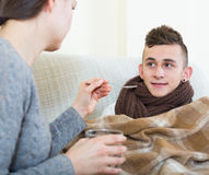 Mother treating teenage boy with syrup at home Royalty Free Stock Photos