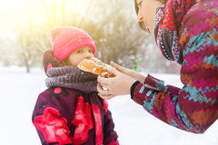 Mother treats daughter with roll. On winter walk Royalty Free Stock Photo