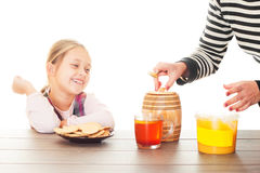 Mother treats the little girl honey Stock Photos