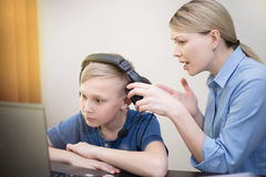 Mother tries to attract the attention of the son working with notebook with headphones. Family relationships stock images
