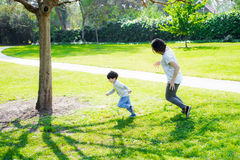 Mother tries to catch her son. In sunny day Royalty Free Stock Photo