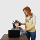 Mother tries to distract son in headphones from computer. Redhead women tries to distract boy in headphones from computer on gray background in square - Modern Stock Photo