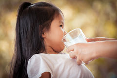 Mother try to give a glass of milk to asian little girl Stock Photos