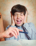 Mother try to help her son with difficult task Stock Photos
