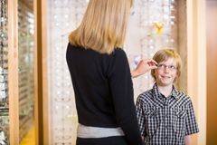 Mother Trying Spectacles On Son At Shop Royalty Free Stock Photography