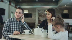 Mother trying to attract father`s attention to daughter while he is busy talking to phone. Mother indignanting. stock video footage