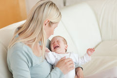 Mother trying to calm her baby Stock Image