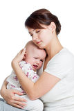 Mother trying to comfort her crying baby isolated Royalty Free Stock Images