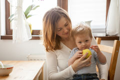 Mother trying to feed an apple to baby boy Stock Image