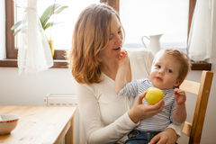Mother trying to feed an apple to baby boy Stock Photography