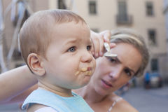 Mother trying to feed her baby boy Stock Photography
