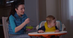 Mother trying to feed her child and he does not want to eat porridge and crying. Indoors stock video
