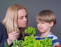Mother trying to feed her son Stock Image