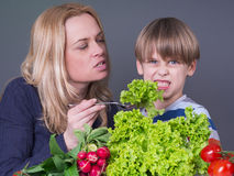 Mother trying to feed her son Stock Photos