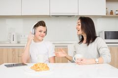Happy family in the morning. Mother trying to say something to her son while he listening music, smiling and doesn`t listen royalty free stock images