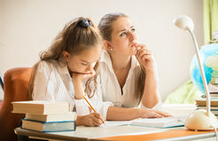 Mother trying to solve complicated exercise with little daughter Royalty Free Stock Photography