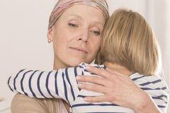 Mother with tumor hugging child Stock Images
