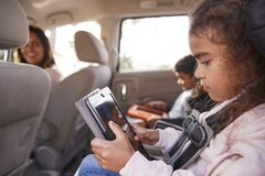 Mother turns around to kids using tablets in the back of car royalty free stock photography