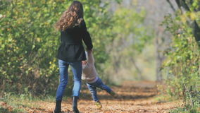 Mother turns baby outdoor. Autumn leaves background. Happy Family Values. Child and mom. Mother's care most important in baby life. Fall season. They are stock video footage