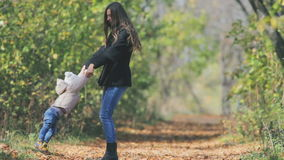Mother turns baby outdoor. Autumn leaves background. Happy Family Values. Mother turns baby outdoor, slow motion. Autumn leaves background. Happy Family Values stock video footage