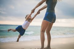 Mom and baby playing near beach. Traveling with family, child. Mother turns her daughter by the arms. Happy Mom and happy child traveling to Asia, at the beach Royalty Free Stock Photography
